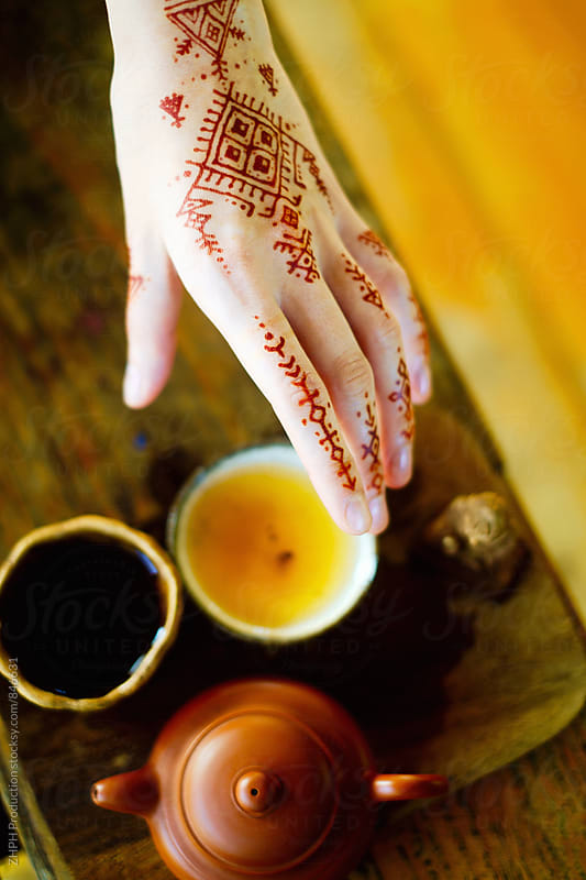 Cup of tea and tattooed hand by ZHPH Production for Stocksy United