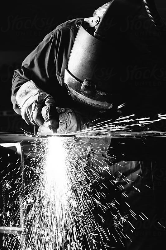 Close up black and white image of steel worker cutting iron with