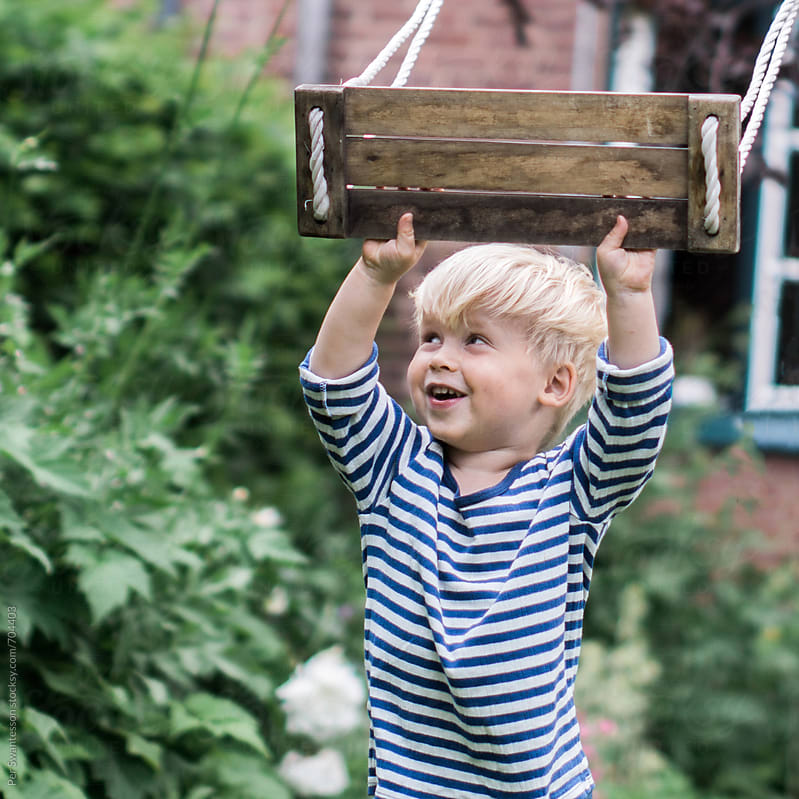 Joyful 3 year old boy playing with a swing  by Per Swantesson for Stocksy United