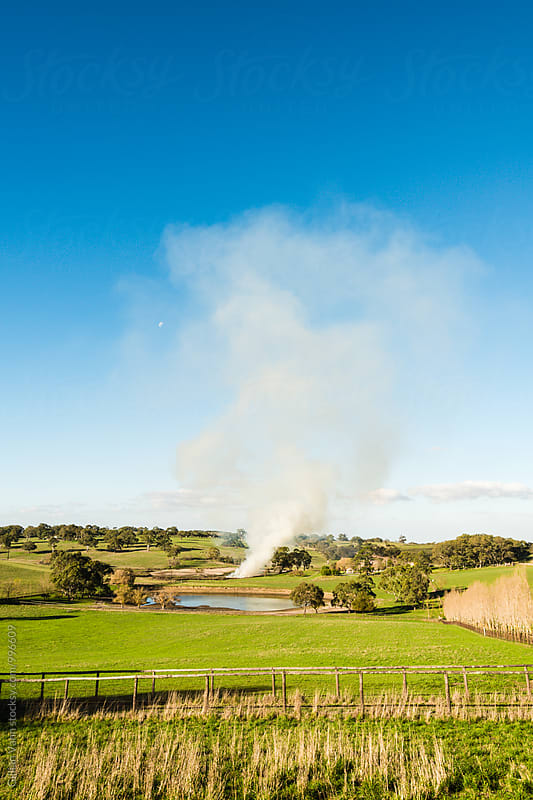 fire on a farm by Gillian Vann for Stocksy United