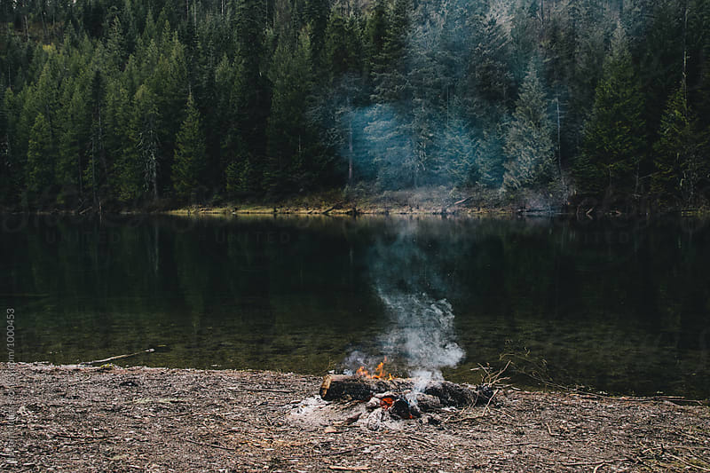 Deserted campfire near on a lake shore by Justin Mullet for Stocksy United
