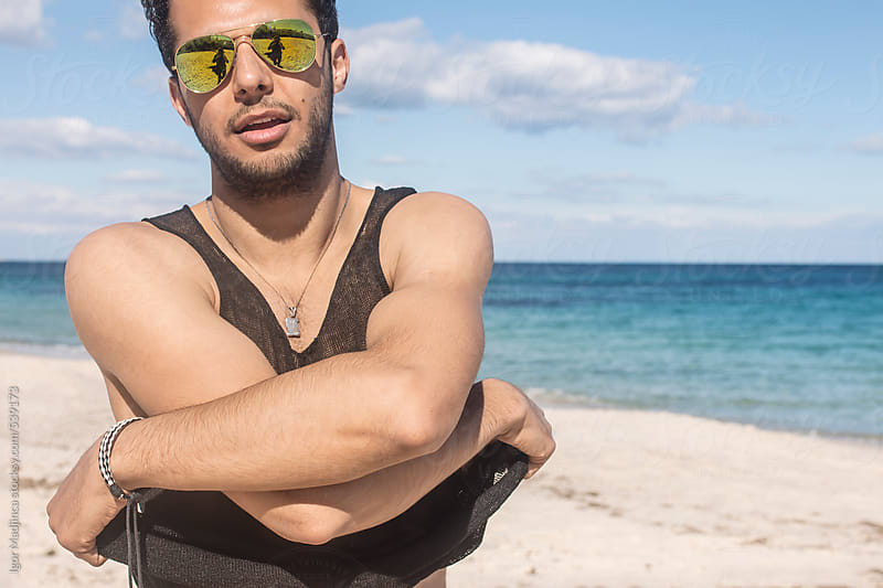 handsome young man get undressed on a sunny beach near the sea by Igor Madjinca for Stocksy United