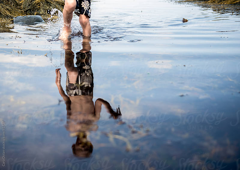 Reflection of a boy playing in a tide pool in the ocean by Cara Dolan for Stocksy United
