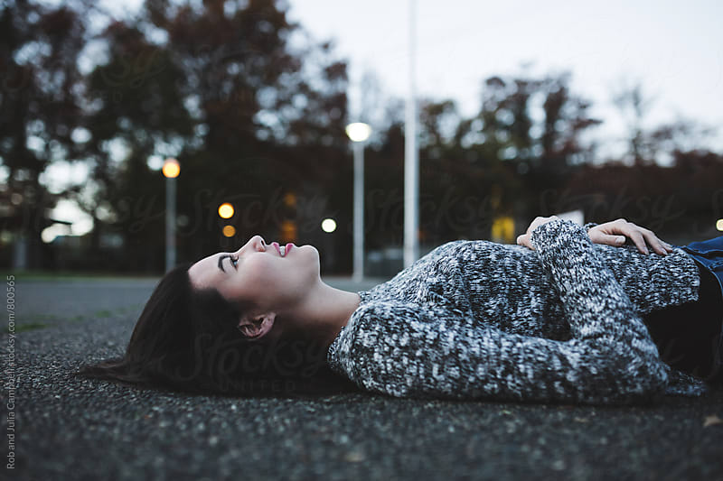 Young black haired woman lying down on sidewalk by Rob and Julia Campbell for Stocksy United