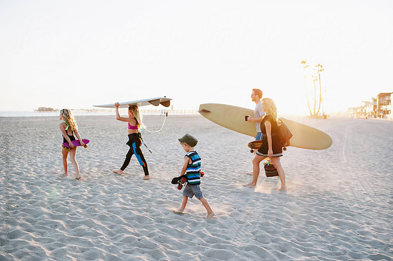 Family walking on sand in beach holding surfboards and bags and skateboards at golden hour by Kristin Rogers Photography for Stocksy United