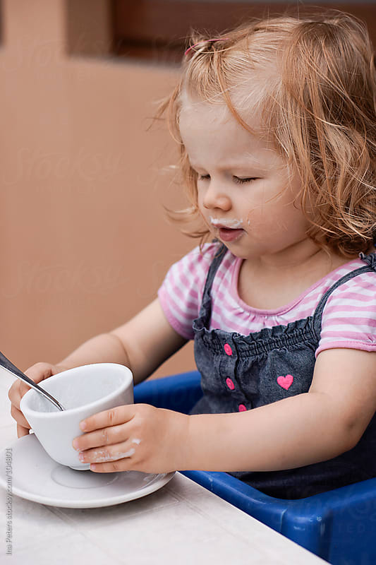 Little girl drinking her milk by Ina Peters for Stocksy United
