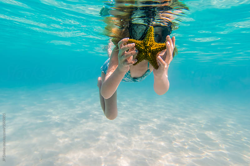 Little Girl WIth Starfish Swimming Snorkeling Underwater at All Inclusive Caribbean Resort White Sand Beach by JP Danko for Stocksy United