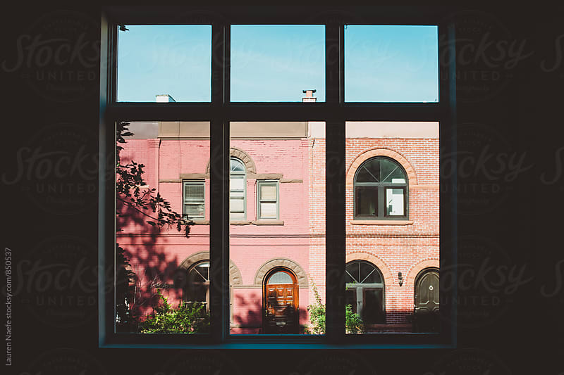Beautiful brownstone seen through a window by Lauren Naefe for Stocksy United