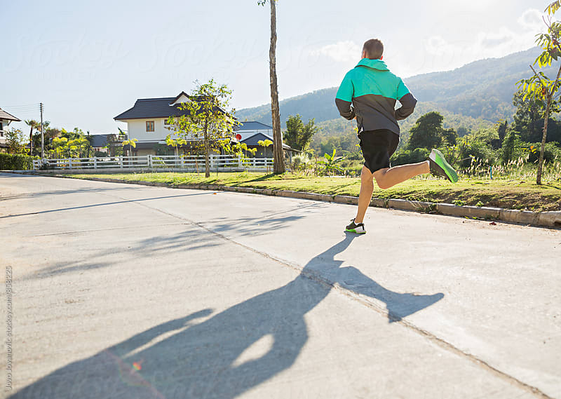 Back of a fit and healthy young male running on the road in the countryside  by Jovo Jovanovic for Stocksy United