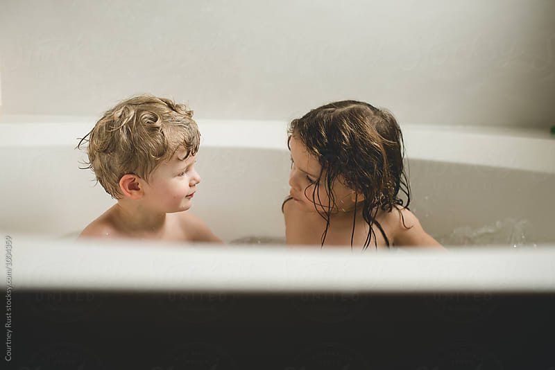 Brother and sister talking during bath time  by Courtney Rust for Stocksy United