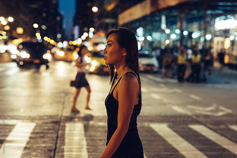 Asian woman crossing the road at night by Good Vibrations Images for Stocksy United