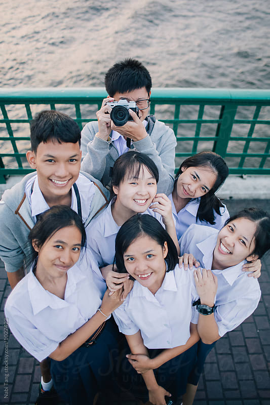 Group of young Thai student portrait on the bridge over the river in Bangkok by Nabi Tang for Stocksy United