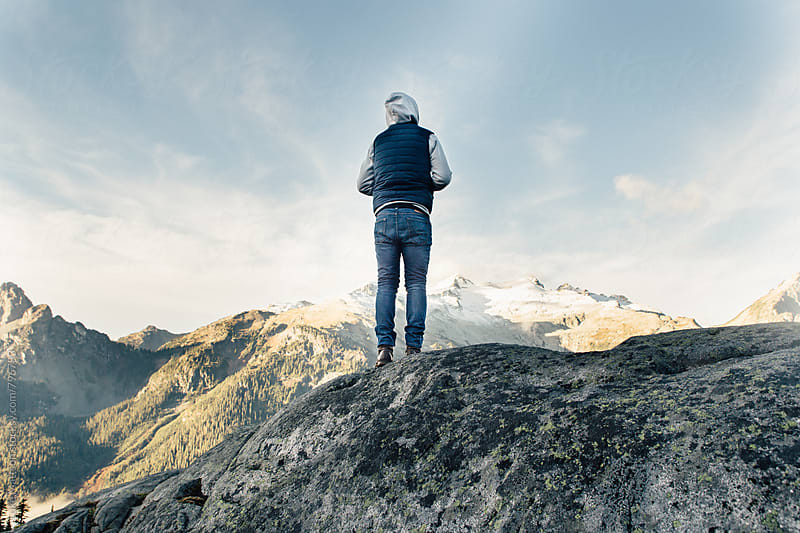 Young Man In Blue Jeans Standing On Top Of Ledge Looking At Mountains by Luke Mattson for Stocksy United