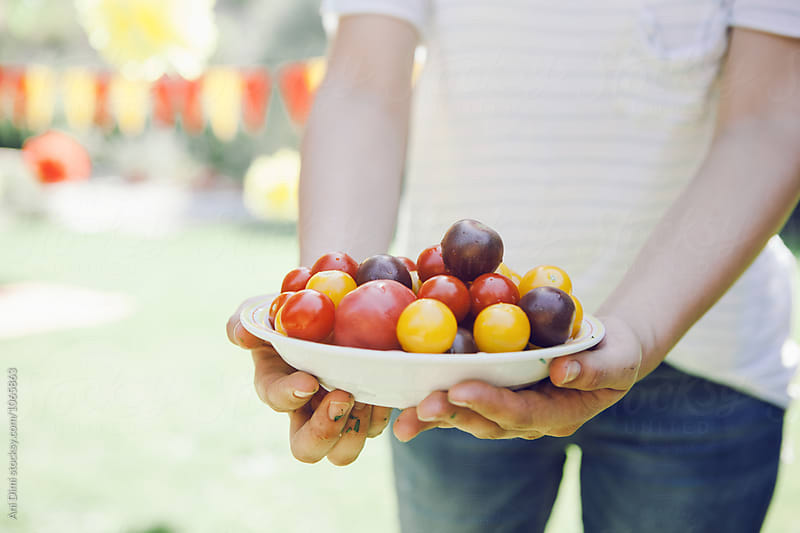 Woman holding a plate with small, red tomatoes. by Ani Dimi for Stocksy United
