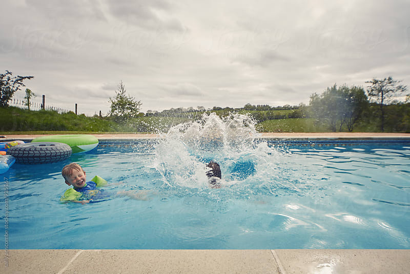 Father and son playing in the swimming pool on holiday by sally anscombe for Stocksy United