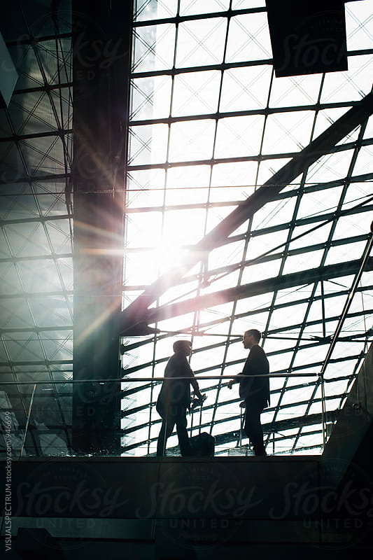 Silhouette of Two Business Travelers Talking in Bright Modern Building by VISUALSPECTRUM for Stocksy United