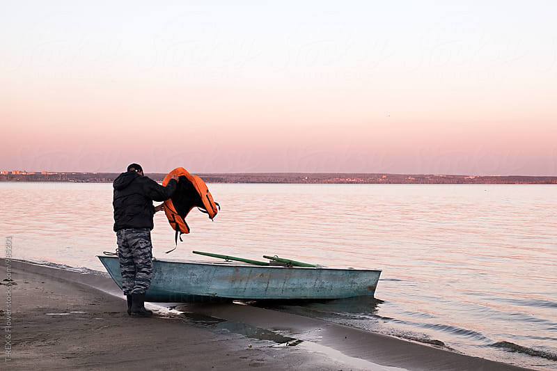 Man near ship holding lifejacket by Danil Nevsky for Stocksy United