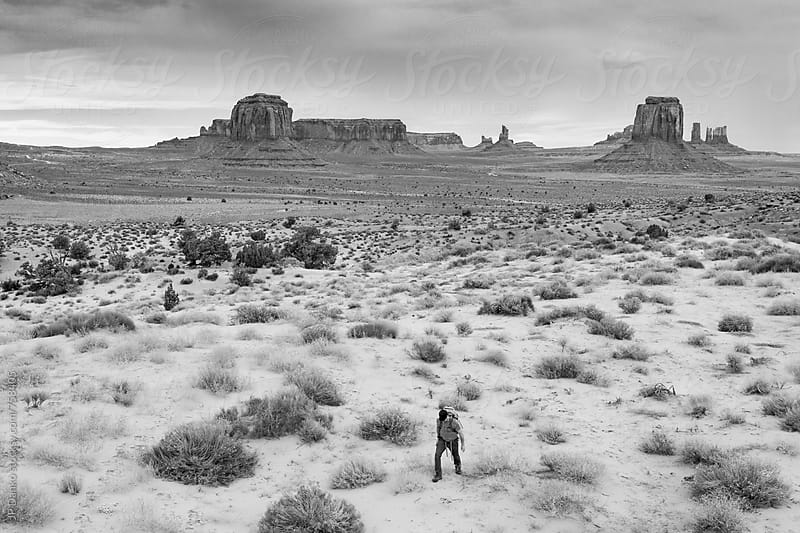 Backpacker Hiking Through Monument Valley Utah USA Black and White Under Cloudy Dramatic Desert Sky by JP Danko for Stocksy United