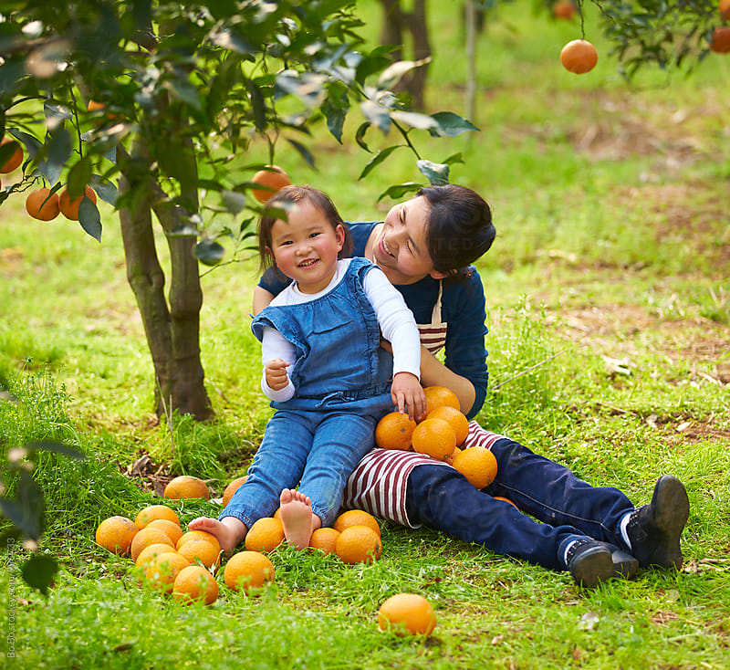 lovely little asian girl with her mother in the orange farm by Bo Bo for Stocksy United