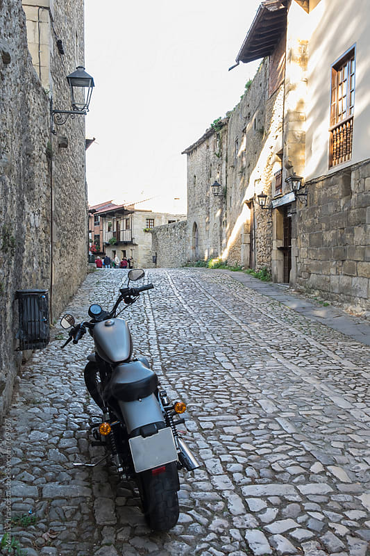 Motorcycle in a medieval town by Marilar Irastorza for Stocksy United