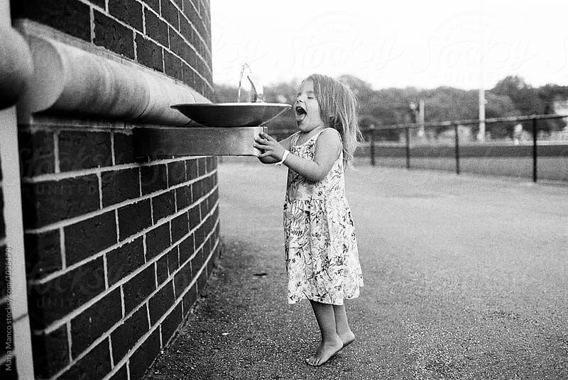 little girl tries to get drink from fountain by Maria Manco for Stocksy United