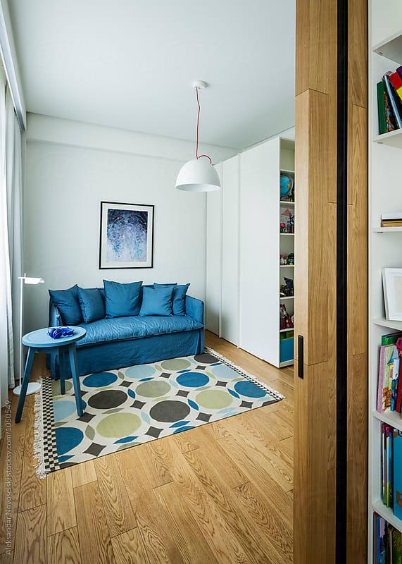 Blue sofa in child's bedroom by Aleksandar Novoselski for Stocksy United