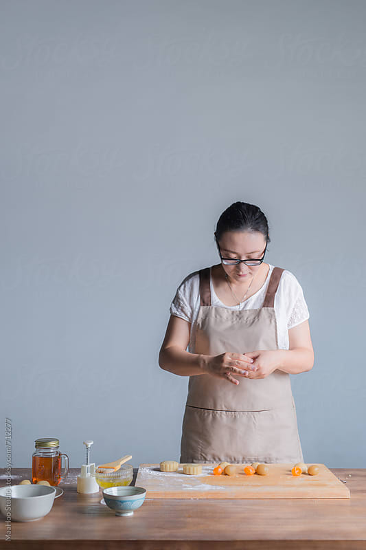 A young woman is making moon cake at home by Maa Hoo for Stocksy United