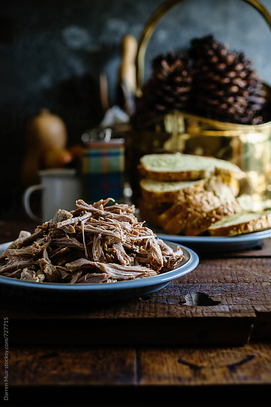 A plate of pulled pork with cornbread in the background. by Darren Muir for Stocksy United