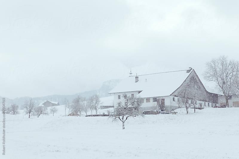 Farm house in winter landscape by Robert Kohlhuber for Stocksy United