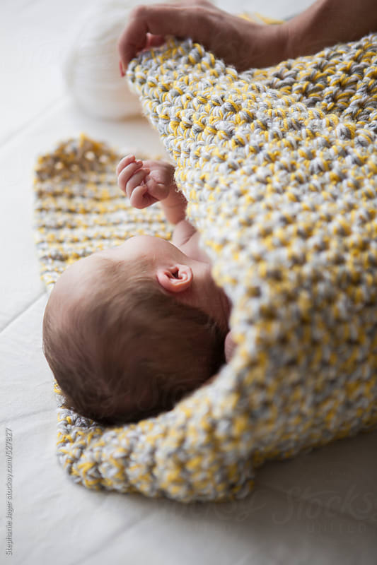 Newborn baby swaddled by Stephanie Jager for Stocksy United