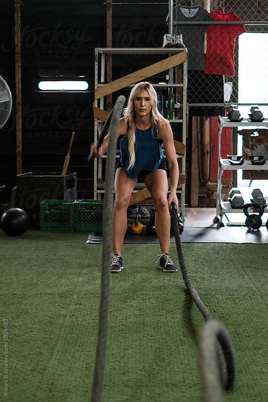 Attractive woman in gritty gym using battling ropes by Riley J.B. for Stocksy United
