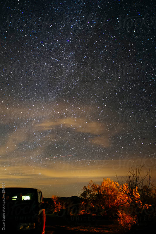 Car in front of milky way by Oscar Lopez for Stocksy United