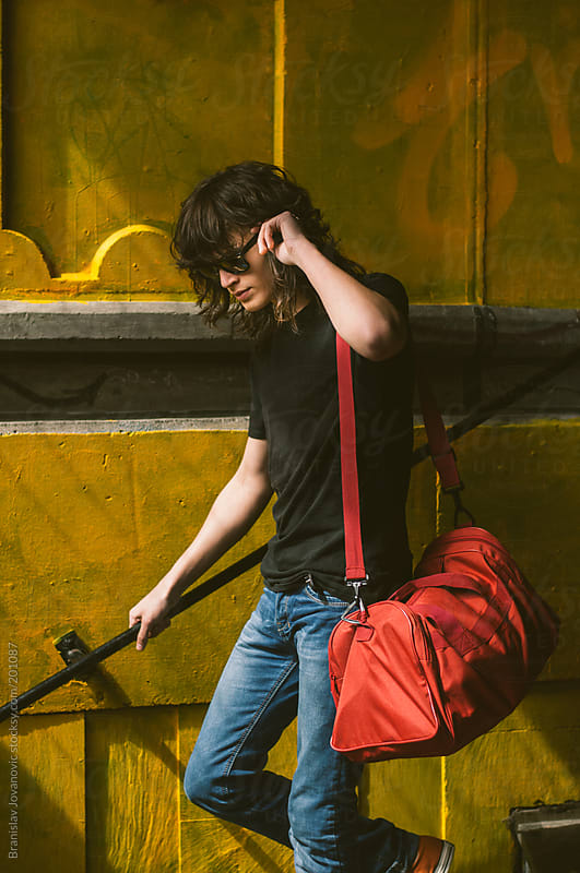 Young man with red traveling bag going down the stairs by Brkati Krokodil for Stocksy United