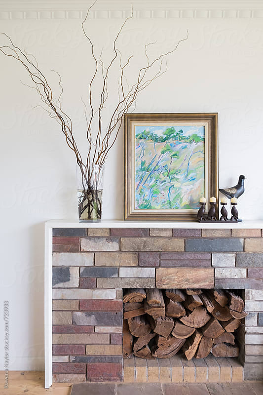 Styled fireplace with artwork and firewood by Rowena Naylor for Stocksy United