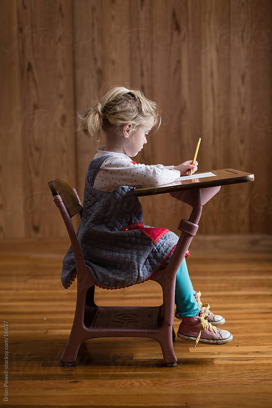 girl in a old school desk by Brian Powell for Stocksy United