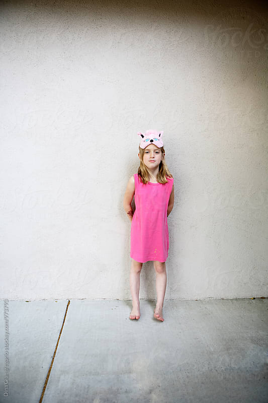 Tiny Girl With Mask On Forehead in Pink Dress by Dina Giangregorio for Stocksy United