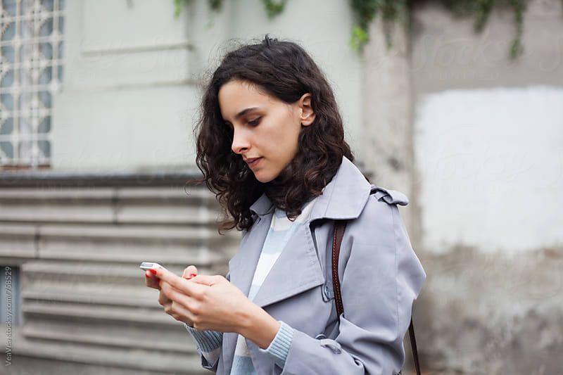 Stylish woman browsing on her mobile phone in the street  by VeaVea for Stocksy United