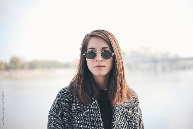 Portrait of a young woman with sunglasses outdoors by Marija Mandic for Stocksy United