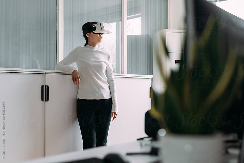 Woman wearing virtual reality headset by MaaHoo Studio for Stocksy United