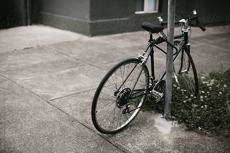 bike parked on sidewalk locked to post by Nicole Mason for Stocksy United