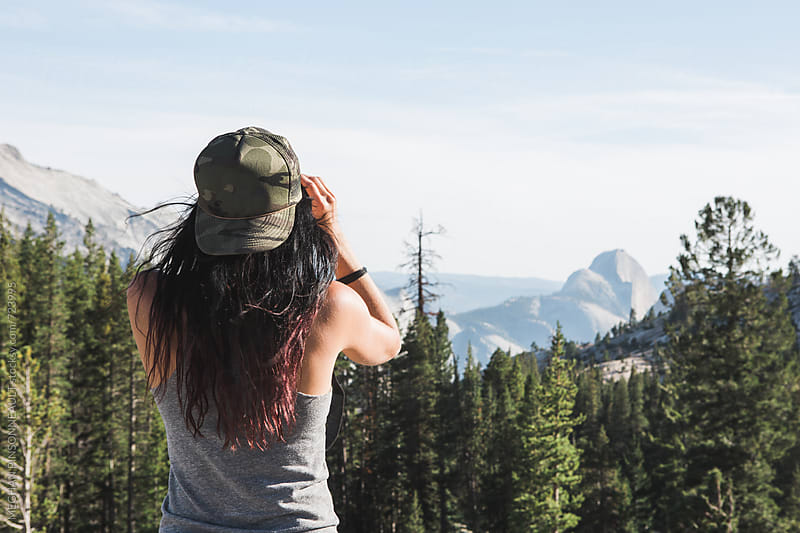Woman with Binoculars Peering Out at Half Dome  by MEGHAN PINSONNEAULT for Stocksy United