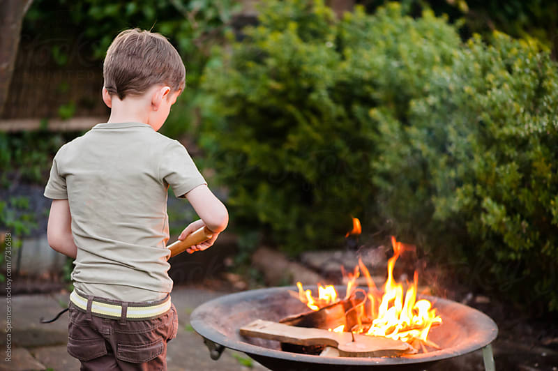 Young child playing with fire by Rebecca Spencer for Stocksy United