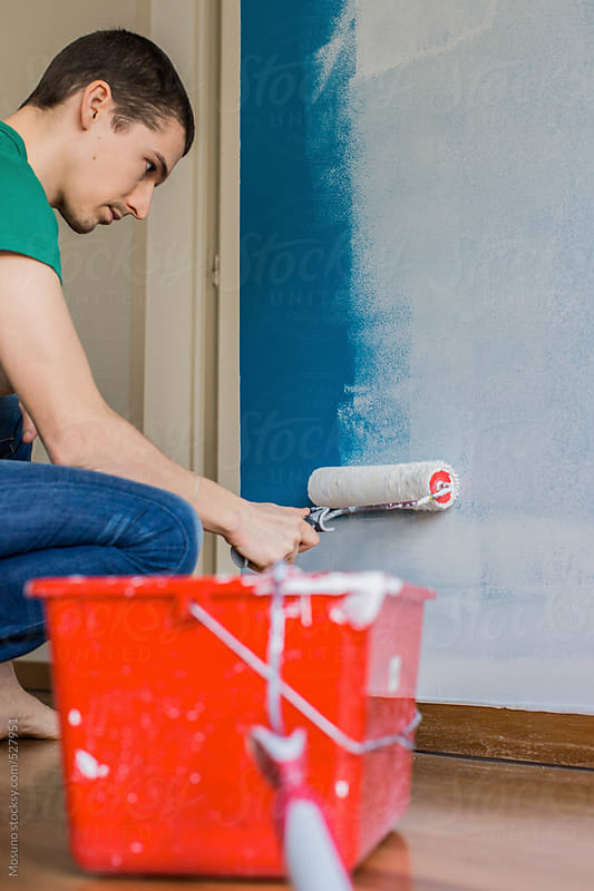 Young Man Painting Blue Wall in His Home by Mosuno for Stocksy United