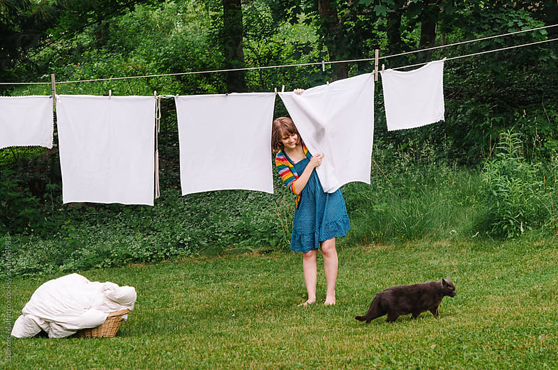 Girl hangs laundry from a clothesline. by Deirdre Malfatto for Stocksy United