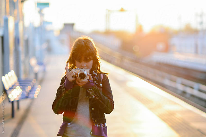 Girl at a station, taking a photo at sunset.  by Kirstin Mckee for Stocksy United