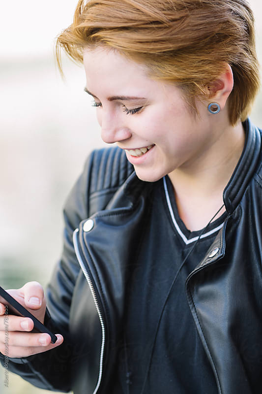 A portrait of a smiling beautiful woman texting with her phone by Alberto Bogo for Stocksy United