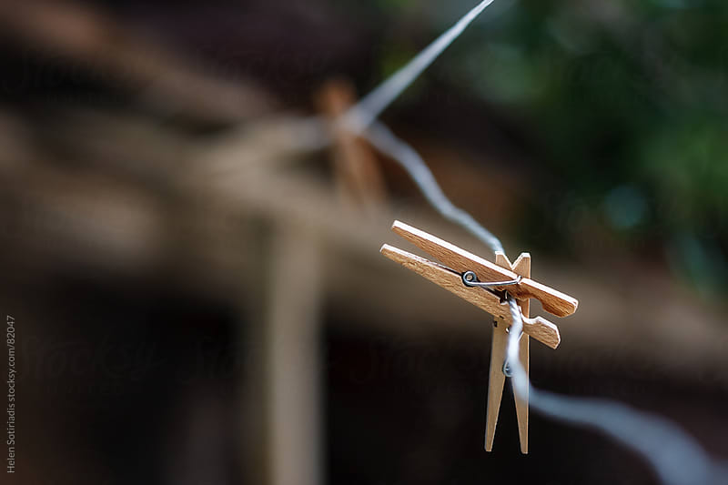 Wood clothespins on a wire by Helen Sotiriadis for Stocksy United