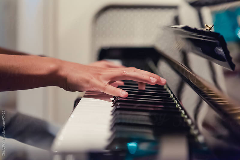 Hands playing on a black piano by Cindy Prins for Stocksy United