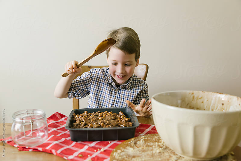 Boy smooths Rocky Road chocolate by Kirsty Begg for Stocksy United