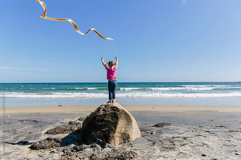 Young Girl Reaching for the sky on Beach by Raymond Forbes LLC for Stocksy United